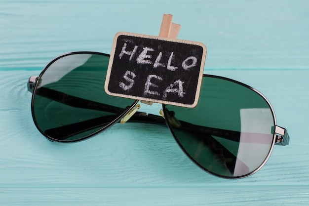 ターコイズブルーの木製の背景に黒板とサングラス。フラットレイをクローズアップ。ネームプレートの海こんにちは。