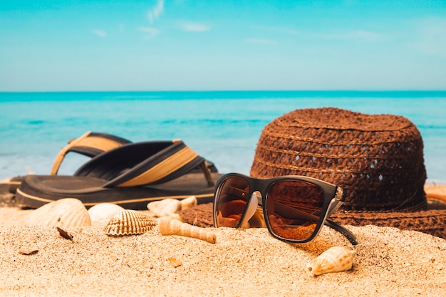 Sunglasses with hat and flip flops on sandy beach