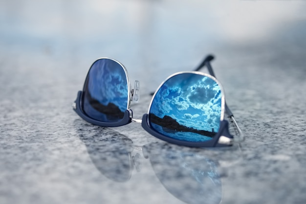 Sunglasses with reflection of the blue sky in glass. selective focus photo.