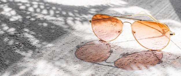 太陽の影が付いたサングラス。夏のレイアウト。女性用サングラス。日焼け止め。