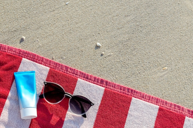 Sunglasses with sunscreen lotion and bag on red towel.