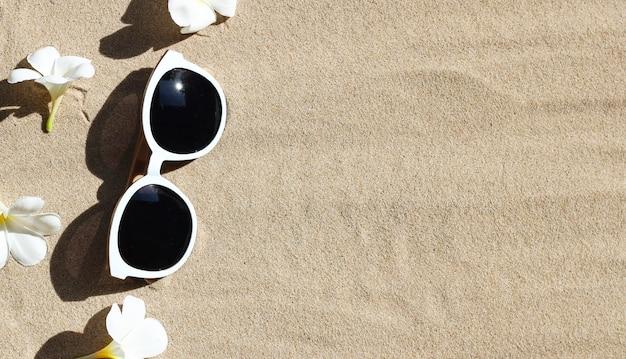 Солнцезащитные очки с белым цветком плюмерии на песке. летний фон концепции.