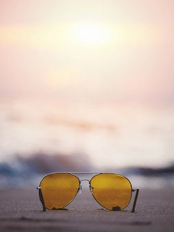Sunglasses with yellow lens on sand at sunset beach.