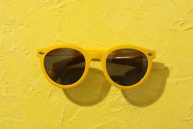 Sunglasses on yellow, close up. summer vacation