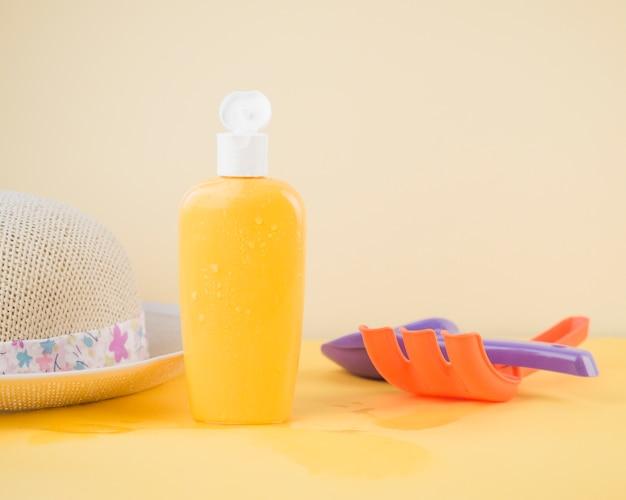Cappello da sole; bottiglia di protezione solare; rastrello e pala giocattolo contro sfondo colorato