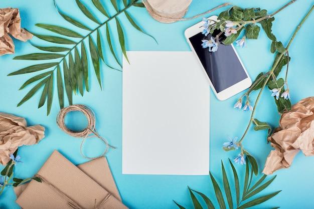 夏の女性のファッション衣装。 sunhat、ギフトボックス、青の背景に熱帯のヤシの枝を持つスマートフォン。ビーチ、休暇、旅行の概念