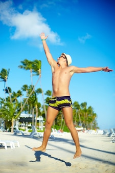 青い空の後ろに青い空の後ろにジャンプビーチでsunhatで幸せなハンサムな筋肉男