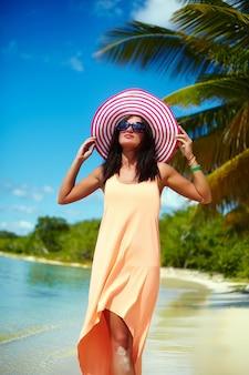 カラフルなsunhatとヤシの近くの暑い夏の日にビーチの海の近くを歩いてドレスで熱い美しい女性