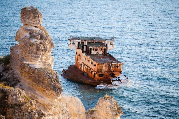 Sunken rusty cargo ship in still blue sea waters with rocks around