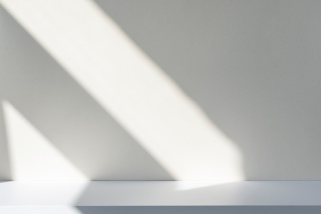 Sunlight and abstract shadows on the wall and white desk. silhouette of lines on blank surface, mockup, space for text.
