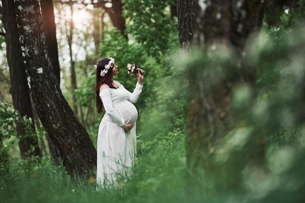 日光と花。ドレスを着た美しい妊娠中の女性は、屋外散歩をしています。肯定的なブルネット