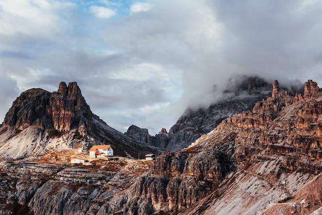Солнечный свет едва проникает сквозь густые облака. туристические постройки ждут желающих пройти через эти удивительные доломитовые горы.