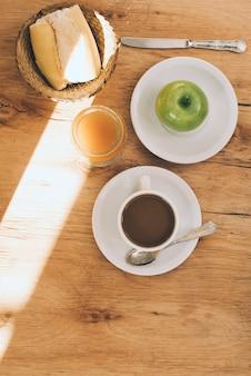 Sunlight over the breakfast on wooden textured background