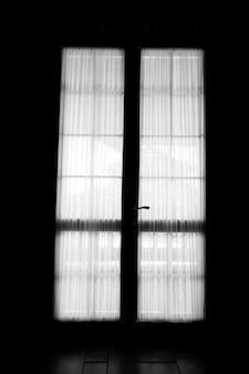暗い部屋で日光のドアの窓