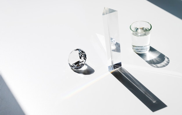 Sunlight falling on diamond; prism and water glass with shadow over white background