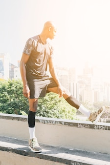 Sunlight over the male runner stretching legs overlooking the buildings in the city