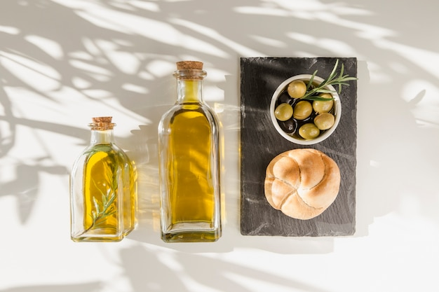 Sunlight over the olive oil bottles with bun and olives on slate plate