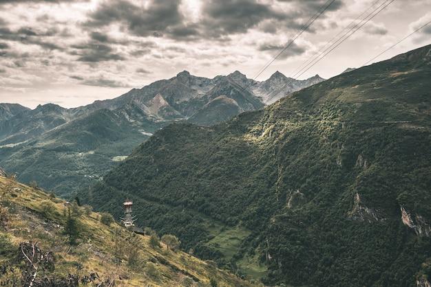Солнечный свет на альпийской долине с горящими горными вершинами и живописными облаками. итальянские французские альпы, летние путешествия, тонированное изображение, винтажный фильтр, тонирование.