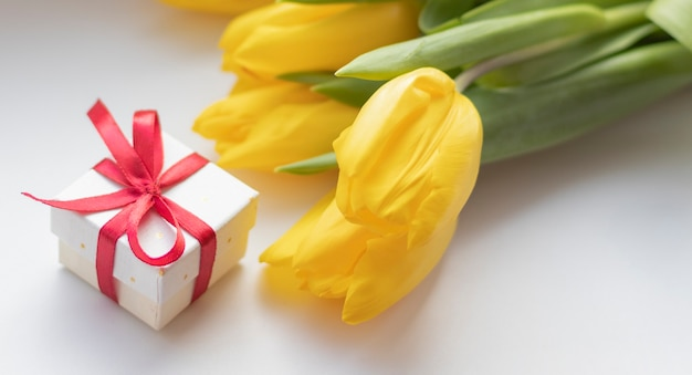 흰색, 어머니의 날 개념에 선물 상자 근처 노란색 튤립에 햇빛