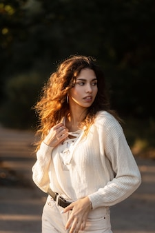 빈티지 니트 옷에 곱슬머리를 한 아름다운 젊은 여성의 햇빛 초상화, 스웨터와 함께 일몰 공원에서 산책