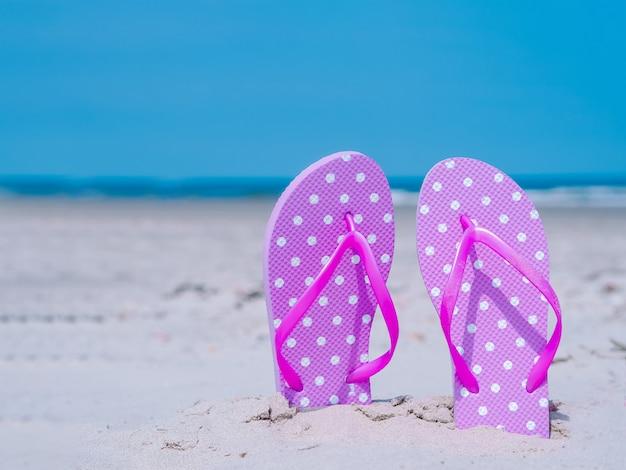 日光の夏の組成物。熱帯の海の砂のビーチサンダル。青い海と空の壁に対して。ビーチアクセサリー、海のツアー、暖かい日当たりの良い夏のビーチアクセサリー夏休みコンセプト