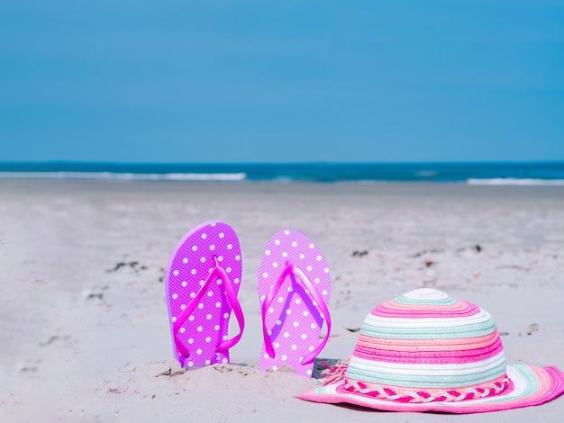 日光の夏の組成物。熱帯の海の砂のビーチサンダル