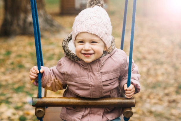 Sunlit little girl in warm clothes on swing