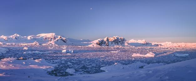 Sunlit snow covered antarctica shoreline.
