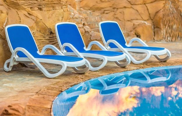 Шезлонги возле бассейна и их отражение в голубой воде