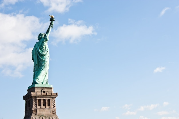 Sunnny day, blue sky with clouds: statue of liberty with copy space