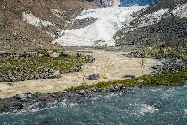 2つのさまざまな山川の合流点がある日当たりの良い高山の風景。美しい澄んだ小川が汚れた川に流れ込みます。豊かな植物の中で2つの異なる川が合流するカラフルな山の風景。