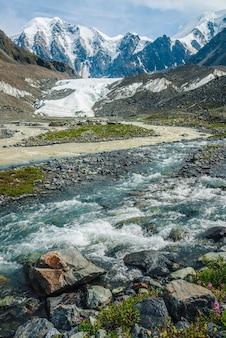 氷河のある雪山を背景に、2つのさまざまな山川が合流する日当たりの良い高山の風景。美しい澄んだ小川が汚れた川に流れ込みます。 2つの異なる川の合流点。
