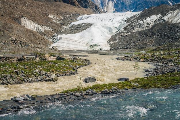 2つのさまざまな山川の合流点がある日当たりの良い高山の風景。