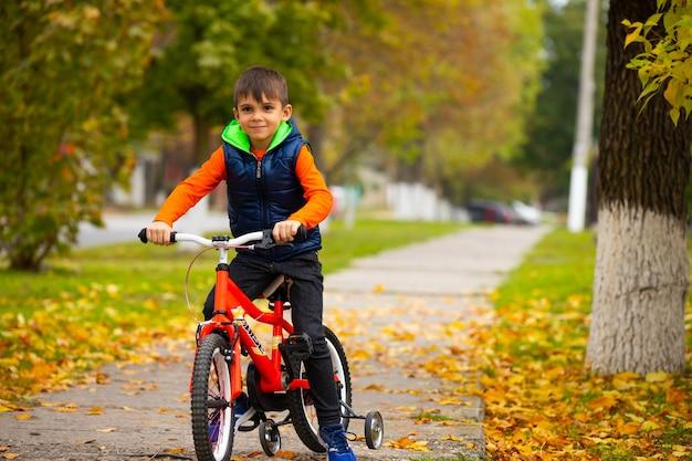 화창한 가을 날. 도시 공원에서 자전거에 소년입니다. 휴식과 재미있는 취미 개념. 빈 공간이있는 사진.