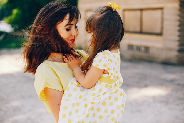 On a sunny beach with yellow sand, mom walks in a yellow dress and her little pretty girl