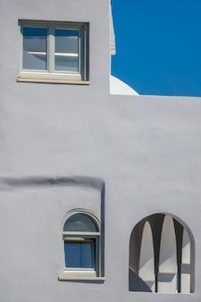 화창한 날과 건물의 회색 돌담. 베란다의 두 개의 다른 창과 여러 개의 아치