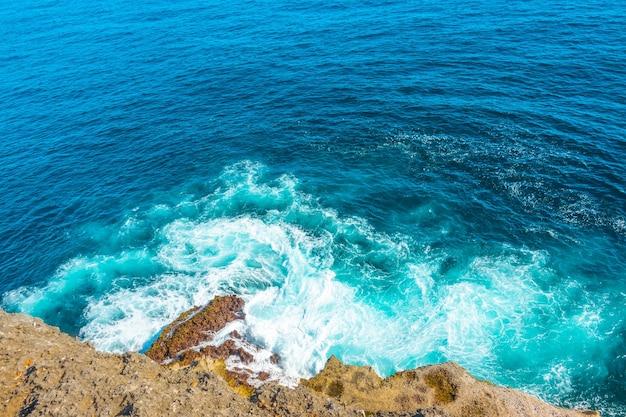 海沿いの晴れた日。泡立つ波の海岸の崖の上からの眺め