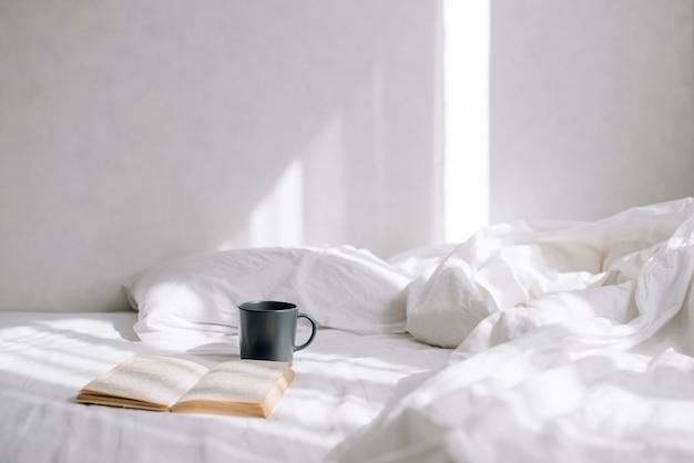 밝은 침실에서 화창한 날. 침대 위에는 커피 한 잔과 책이 펼쳐져 있습니다. 아름다운 아침