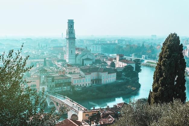Солнечный день в старом городе верона в италии вид сверху на красные крыши башни улицы река