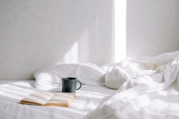 Sunny day in light bedroom. on the bed is a cup of coffee and an open book. beautiful morning