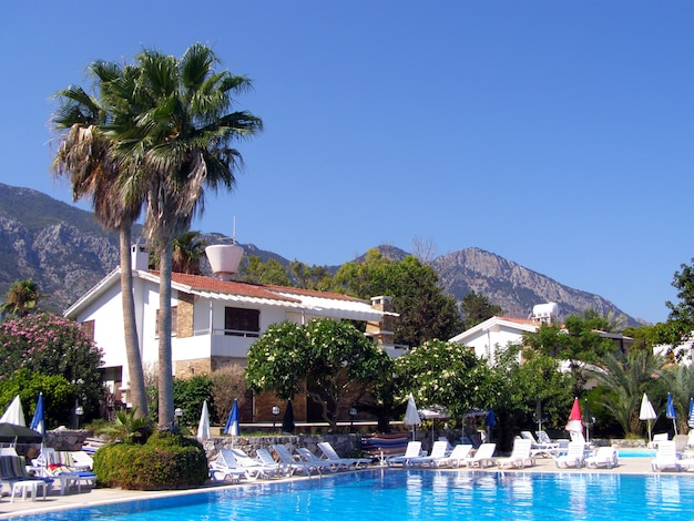 Sunny day on the mediterranean coast and a swimming pool with sun loungers and a beach umbrella