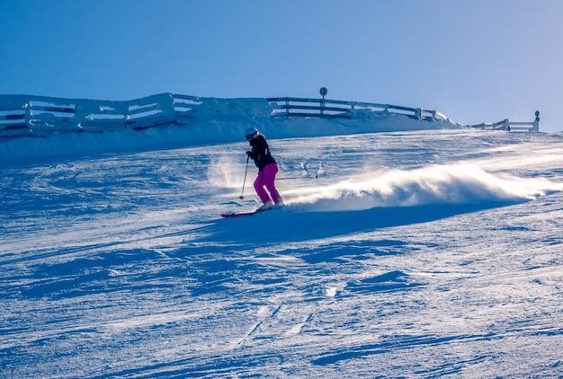 눈 덮인 스키 슬로프에 화창한 날. 인식 할 수없는 여자 스키어가 눈 먼지를 제기