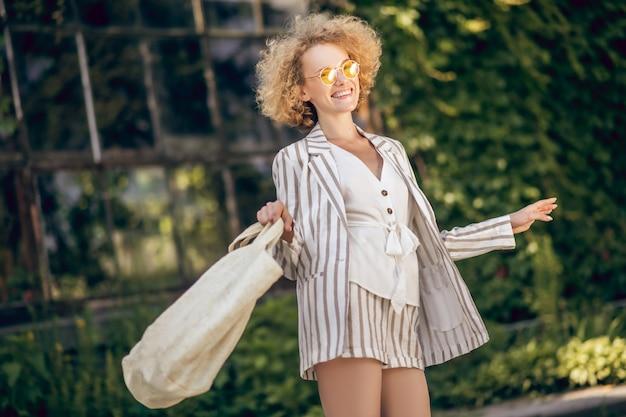晴れた日。手にエコバッグと通りのスリムなかわいい若い女性