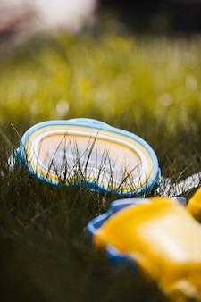 Солнечный день с очками и ластами на траве