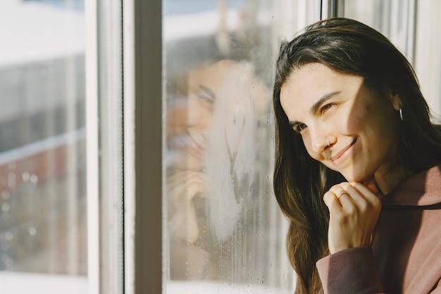 Солнечный день. женщина запрыгивает в окно. теплая одежда