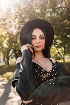 Sunny fresh portrait sexy woman in black beautiful dress in fashionable hat in vintage leather jacket in park on sunny bright day. attractive sexy brunette girl enjoys sunlight on nature in spring day