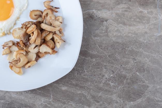 Uovo fritto soleggiato e funghi sul piatto bianco.