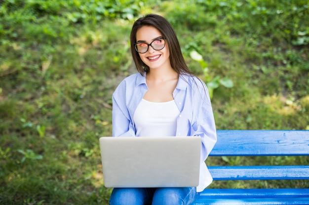 Солнечная девушка в синей футболке сидит на скамейке в парке и использует свой ноутбук