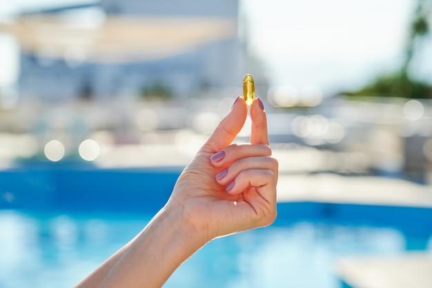 女性の手、背景の太陽の青い水に日当たりの良い黄金のビタミンdオイルカプセルオメガ3。健康的なライフスタイル、栄養補助食品、ダイエット