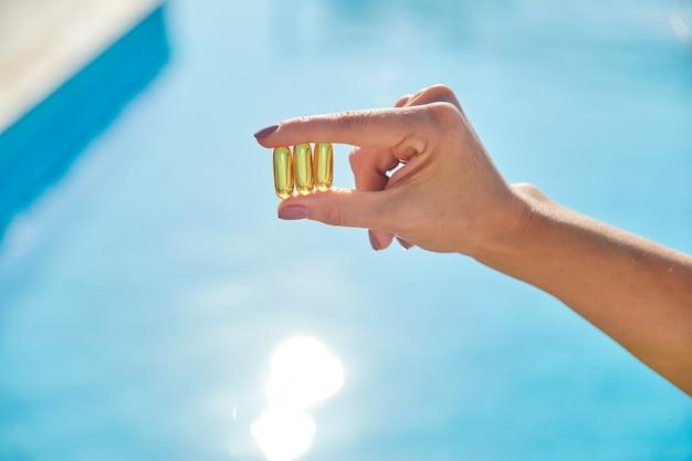 日当たりの良い黄金のビタミンdオイルカプセルオメガ3女性の手、背景の太陽の青い水。健康的なライフスタイル、栄養補助食品、ダイエット